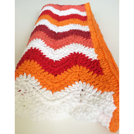 orange crochet blanket on the floor