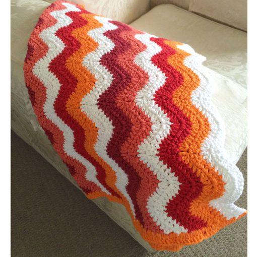 Chevron blanket orange red white on couch